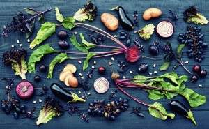Collection of fresh purple fruit and vegetables on the black wooden table